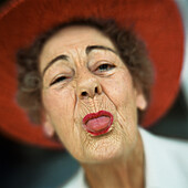 Portrait of senior woman wearing red hat with tongue sticking out