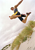 Young man on beach jumping, mid-air, low angle view.