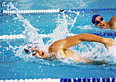 Male swimmers swimming freestyle in pool, close-up