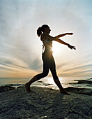 Woman performing tai chi on beach, silhouette