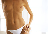 Partially nude woman standing with hand on hip, mid section, close-up.