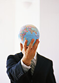 Businessman holding out globe, hiding man's face
