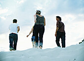 Four people walking on sand, rear view