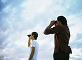Two people looking through binoculars, low angle view