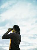 Man looking through binoculars, low angle view