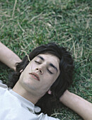 Young man lying on grass with eyes closed and piece of grass in mouth