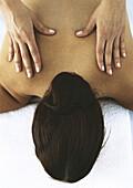 Woman lying face down, having back massaged
