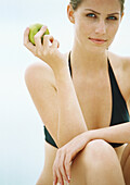 Young woman in bikini holding apple, looking at camera