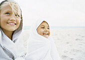 Two girls wrapped up on beach