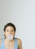 Young woman blowing bubble gum bubble, portrait