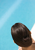 Back of woman's head, pool in background