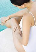 Woman sitting by edge of pool, rubbing leg