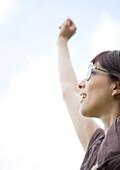 Woman wearing glasses, reaching arm upward
