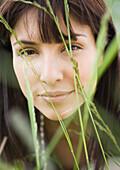 Woman's face seen through blades of grass