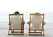 Two people sitting in beach chairs, rear view