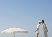 Couple kissing next to parasol