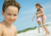 Boy smiling, children playing in background, on beach