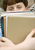 Boy holding stack of school books