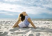 Girl doing yoga pose on beach