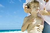 Woman applying sunscreen to son's face on beach