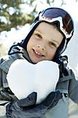 Boy in ski gear holding heart made of snow, portrait