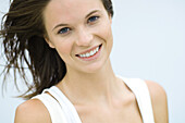 Teenage girl smiling at camera, hair tousled by breeze, portrait