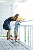 Mother and son standing on porch together, woman holding binoculars and pointing, both looking away