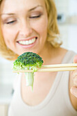 Woman using chopsticks to hold a single piece of broccoli, focus on foreground