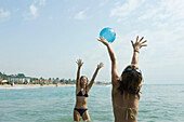 Teen girls playing with beach ball in sea