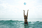 Teen girl in sea with arms raised to catch ball