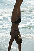 Teen girl doing handstand on beach