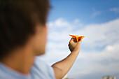 Man throwing paper airplane