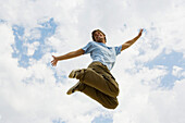 Man jumping joyfully in midair, low angle view