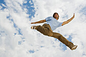 Young man leaping joyfully in midair, low angle view
