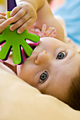 Infant girl chewing on plastic toy, looking at camera