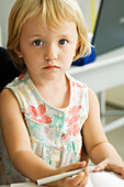 Little girl holding pen, looking at camera