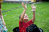 Boy with arms raised showered in falling confetti