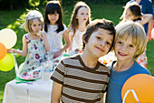 Young friends together at outdoor birthday party, portrait