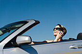 Woman talking on cell phone while driving convertible