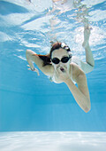Teenage girl in pool, holding nose and wearing goggles, underwater view
