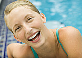 Young woman laughing, pool in background