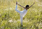 Woman standing in shiva posture in field