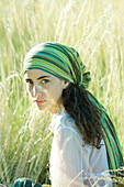 Young hippie woman in field, looking at camera, portrait