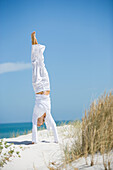 Young woman doing handstand on dune, overlooking ocean
