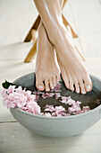 Young woman's feet and floral foot bath