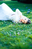 Teenage girl lying in grass, touching face, looking at camera