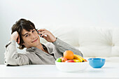 Man sitting at coffee table, using cell phone, smiling at camera