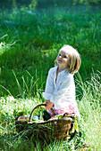 Little girl holding large basket full of fresh produce