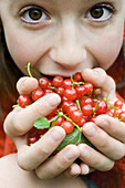 Teenage girl holding up large handful of red currants, close-up