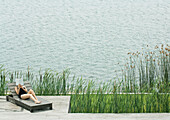 Woman reclining on lounge chair, reading, next to lake